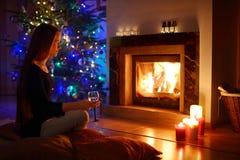 妇女喝一杯由壁炉在圣诞节的a 免版税库存图片