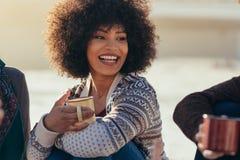 妇女喝与朋友的咖啡在海滩 库存图片
