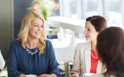 妇女喝咖啡和谈话在餐馆 免版税库存图片
