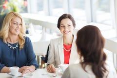 妇女喝咖啡和谈话在餐馆 免版税图库摄影
