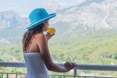 妇女喝在旅馆阳台的橙汁 免版税库存图片