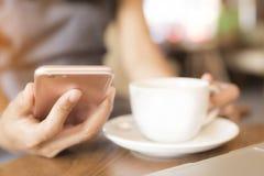 妇女喝她使用电话传达的咖啡 免版税库存图片