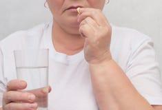 妇女喝对待甲状腺,消灭根瘤和正常化的激素一个荷尔蒙药片,治疗,特写镜头 免版税库存照片