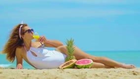 妇女喝新橙汁过去背景海 年轻美女说谎由沙子的海的,饮料 影视素材