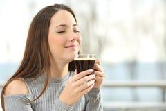 妇女嗅到的咖啡芳香 免版税库存照片
