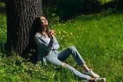 妇女嗅到的花坐草坪 免版税库存照片