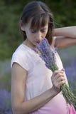 妇女嗅到的花束淡紫色 免版税库存图片