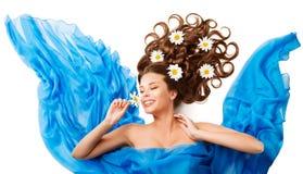 妇女嗅到的花,愉快的女孩开花在布料的发型 库存照片