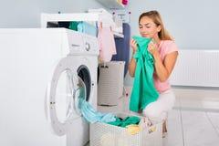 妇女嗅到的衣裳在洗涤以后 免版税库存照片