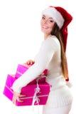 妇女圣诞老人有许多桃红色礼物盒的帮手帽子 库存照片