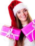 妇女圣诞老人有许多桃红色礼物盒的帮手帽子 库存图片