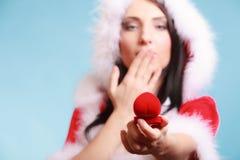妇女圣诞老人服装拿着有圆环的礼物盒在蓝色 库存图片