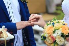 妇女在一个人上把定婚戒指放 免版税库存图片