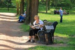 妇女在一个公园读一张报纸在Kislovodsk 库存照片