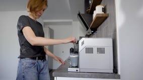 妇女在一个咖啡机器投入容器牛奶在家庭厨房里并且交换它在早晨时间 股票录像