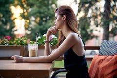 妇女在一个咖啡馆在夏天坐一个大阳台在城市,拿铁 库存照片
