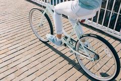 妇女在一个夏天早晨骑一辆蓝色城市自行车 库存图片