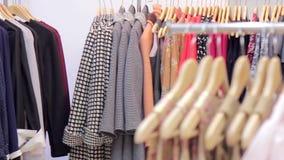 妇女在一个挂衣架的` s衣物在精品店 股票录像