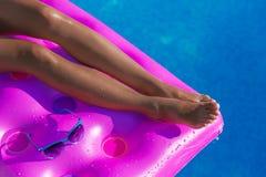 妇女在一个气垫的` s腿在游泳池 免版税库存图片