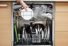 妇女在一个现代厨房使用一台洗碗机 免版税图库摄影
