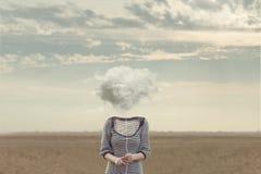 妇女在一个超现实的情况的一朵软的云彩替换的` s头 免版税图库摄影