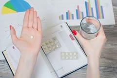 妇女在一只手和一块玻璃上的拿着一个药片在水在别的上 免版税库存照片