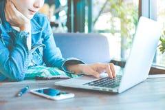 妇女在一台便携式计算机的手工在办公室 免版税库存照片
