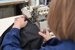 妇女在一台电缝纫机缝合 库存照片