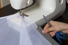 妇女在一台缝纫机工作 她缝合在窗口的帷幕 使用统治者,它做测量并且切开织品 免版税库存图片