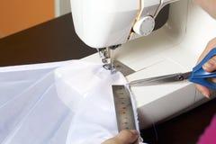 妇女在一台缝纫机工作 她缝合在窗口的帷幕 使用统治者,它做测量并且切开织品 库存照片