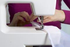 妇女在一台缝纫机工作 她缝合在窗口的帷幕 免版税库存照片