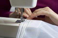 妇女在一台缝纫机工作 她缝合在窗口的帷幕 免版税库存图片