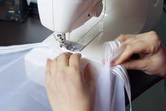 妇女在一台缝纫机工作 她缝合在窗口的帷幕 库存照片