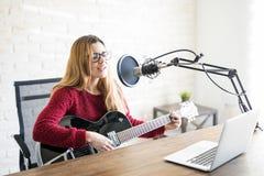 妇女在一台网上收音机的音乐家广播 免版税库存照片