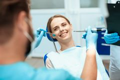 妇女在一把牙齿椅子,医生牙医坐弯曲在她 免版税库存照片