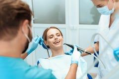 妇女在一把牙齿椅子,医生牙医坐弯曲在她 库存图片