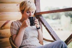 妇女在一把藤椅坐有一杯茶的一个阳台 库存图片