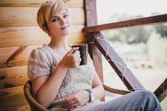 妇女在一把藤椅坐有一杯茶的一个阳台 免版税图库摄影