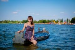 妇女在一条老木小船坐一个大湖Svityaz 夏天的概念 库存图片
