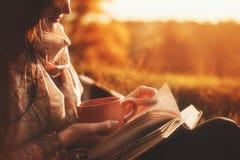 妇女在一棵树附近坐在秋天公园并且拿着一本书和一个杯子有一份热的饮料的在她的手上 登记女孩读取 免版税库存照片