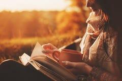 妇女在一棵树附近坐在秋天公园并且拿着一本书和一个杯子有一份热的饮料的在她的手上 登记女孩读取 免版税库存图片