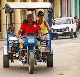 妇女在一辆小摩托车驾驶的出租汽车乘坐 免版税库存图片