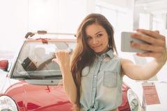 妇女在一辆新的汽车的作为selfie在陈列室 免版税库存照片