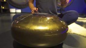 妇女在一间黑暗的凝思屋子演奏冥想的仪器坦克鼓 特写镜头 股票录像