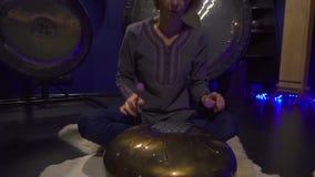 妇女在一间黑暗的凝思屋子演奏冥想的仪器坦克鼓 股票视频