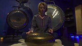 妇女在一间黑暗的凝思屋子演奏冥想的仪器坦克鼓 股票录像