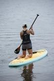 妇女在一paddleboard下跪在多沼泽的支流 免版税库存图片