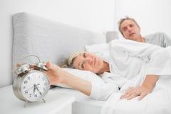 妇女在与关闭闹钟的伙伴的床上 免版税库存图片