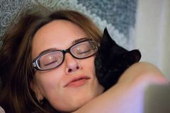 妇女在与小猫的床上 免版税库存图片