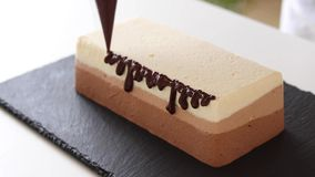 妇女在与巧克力釉的巧克力乳酪蛋糕装饰 免版税图库摄影